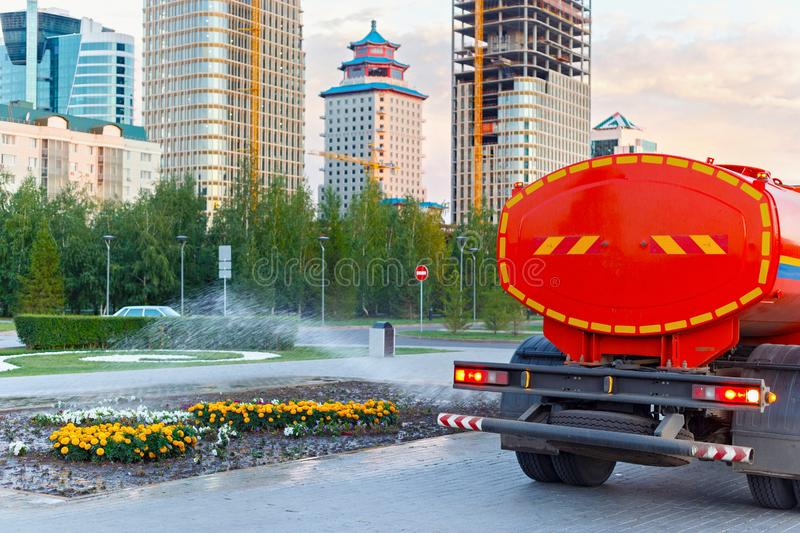 Watering the flowers with public service car. And modern buildings on the background royalty free stock image