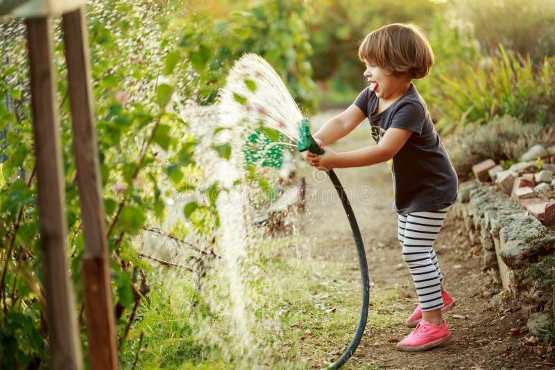 Watering garden. Little happy girl watering garden royalty free stock photography