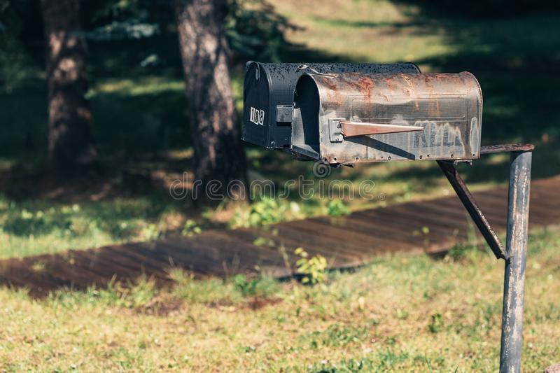 Watering garden near the old house in the small town. Mail box in front of the house.  stock photography
