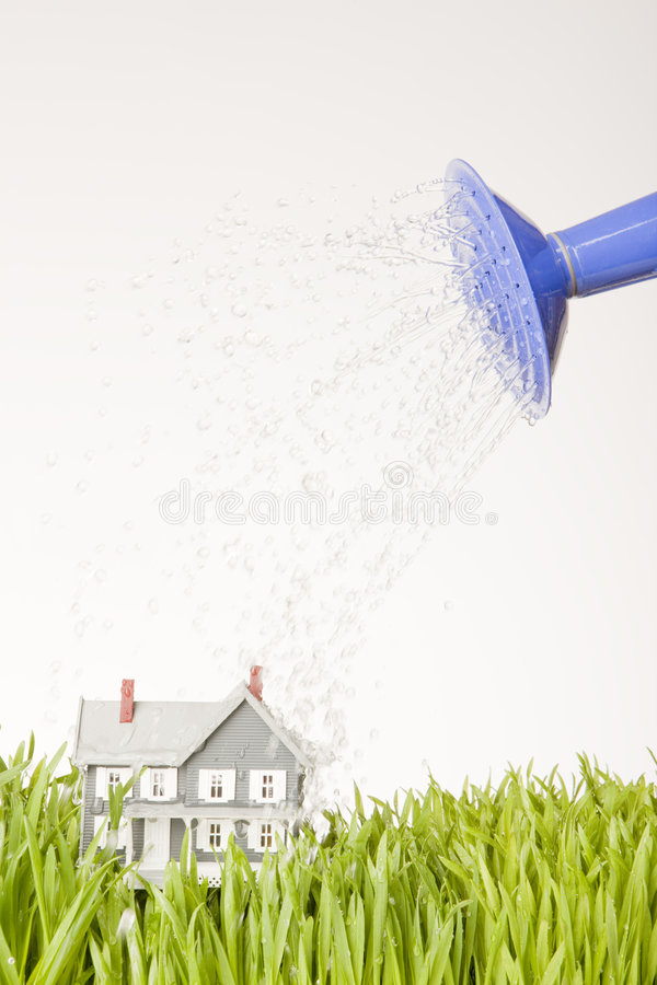 Watering House. Model house being watered by blue watering can on fresh green grass vertical image stock image