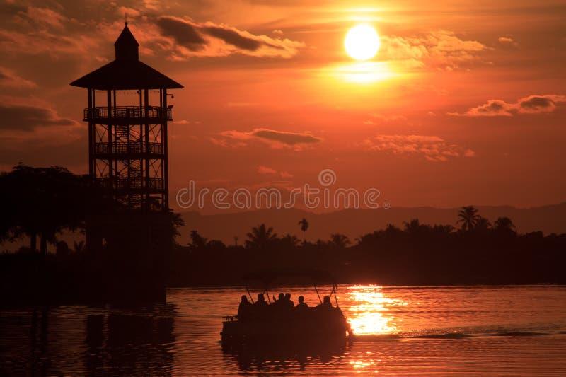 Waterkant Kuching met Silhouetboot stock foto's