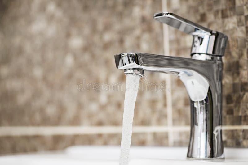 Waterkraan die in de badkamers stromen De open wasbak van de chroomtapkraan stock afbeelding