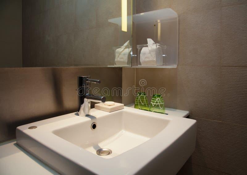 Waterkraan en Ceramische Witte Gootsteen in een Moderne WC met Bruine Tegels stock foto's