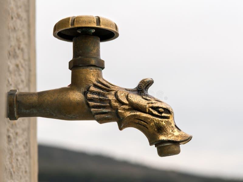 Waterkraan van bronsvorm wordt gemaakt van een draak die stock afbeelding