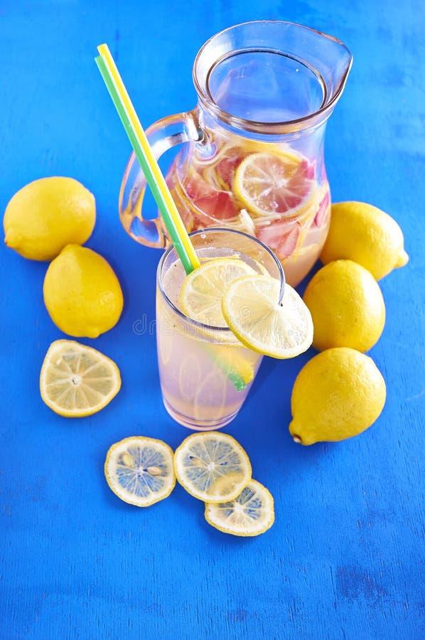 Waterkruik limonade met citroenen, en vers stock fotografie
