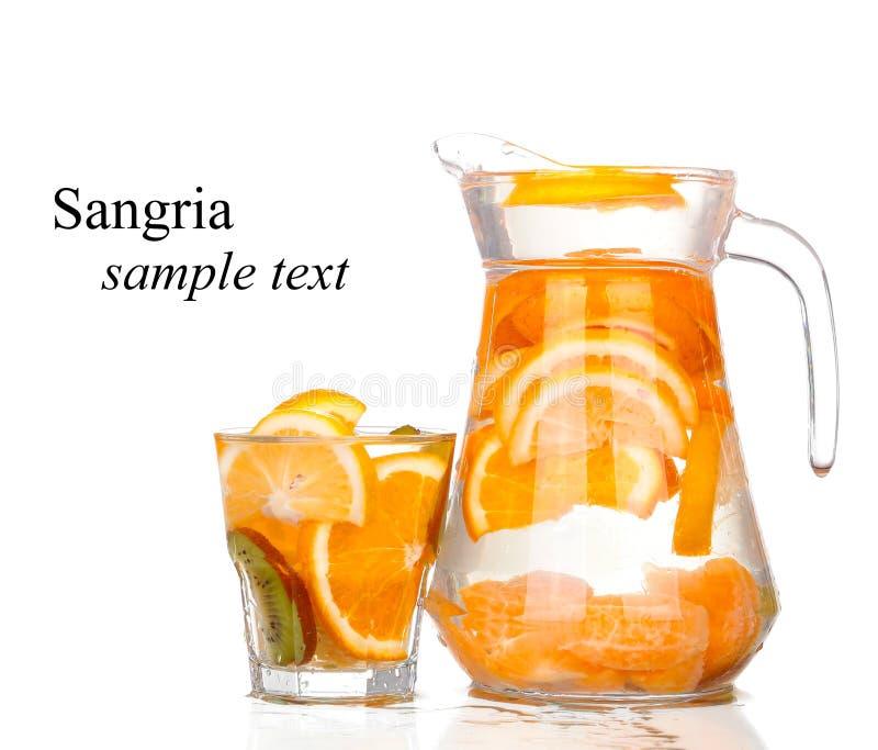 Waterkruik met een verfrissende drank met citroenplakken van sinaasappel en kiwi op witte achtergrond royalty-vrije stock foto's