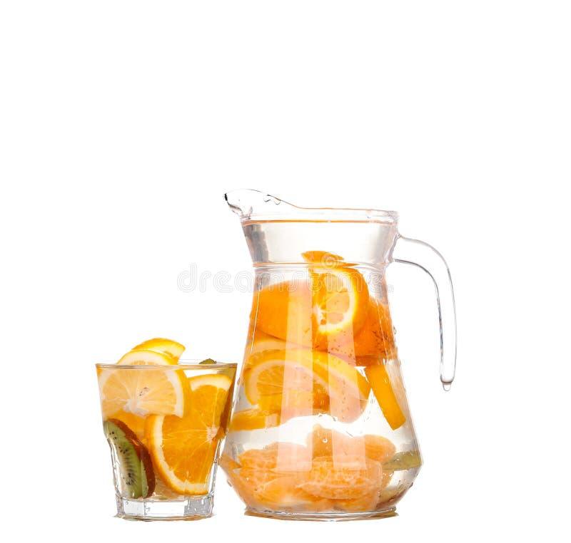 Waterkruik met een verfrissende drank met citroenplakken van sinaasappel en kiwi op witte achtergrond stock foto