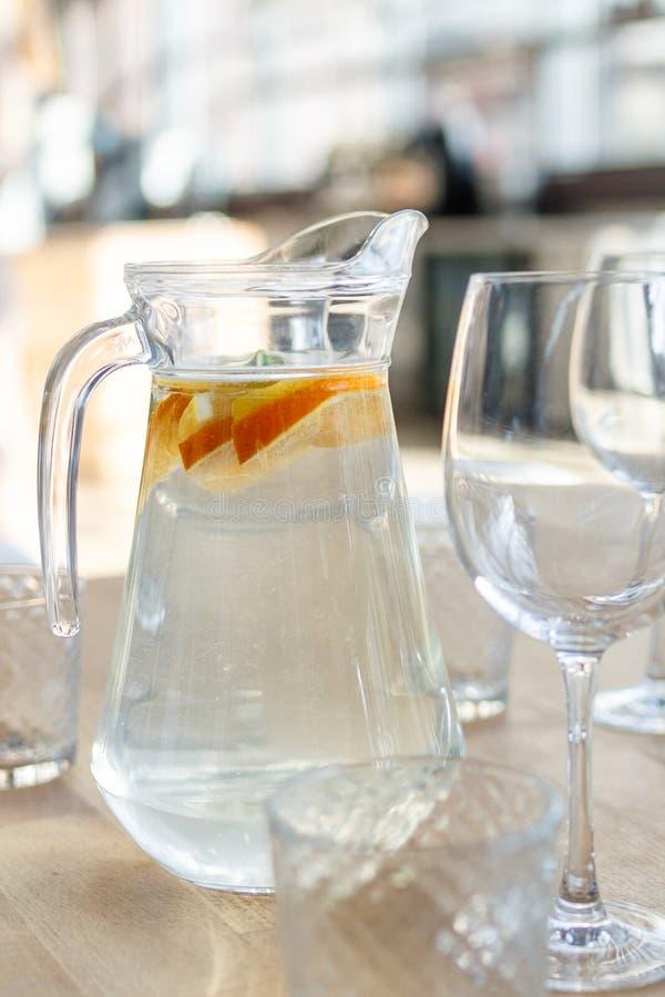 Waterkruik van eigengemaakte limonadedrank van sodawater, citroen, oranje en verse muntbladeren op houten lijst met glazen stock afbeelding