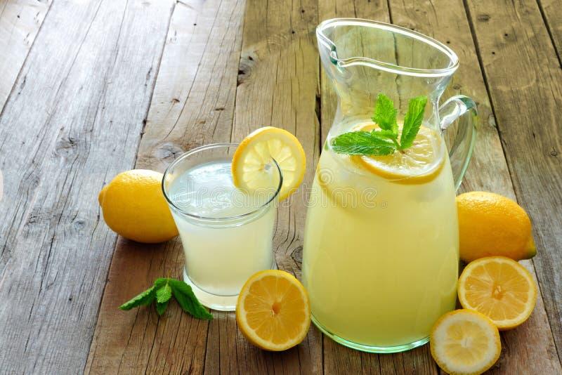 Waterkruik verse limonade met gevuld glas op houten stock foto