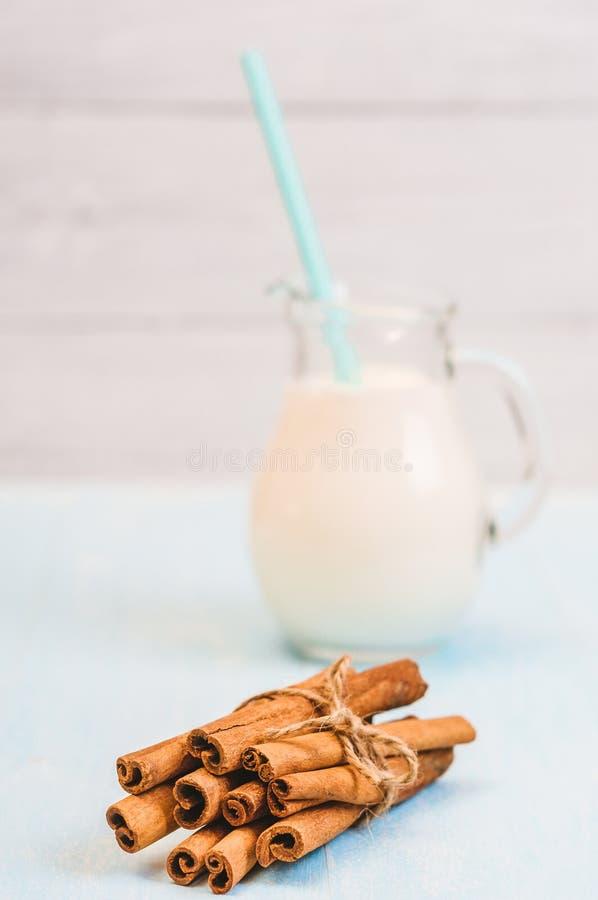 Waterkruikglas melk met kaneel en cocktailbuis op blauwe houten achtergrond royalty-vrije stock foto