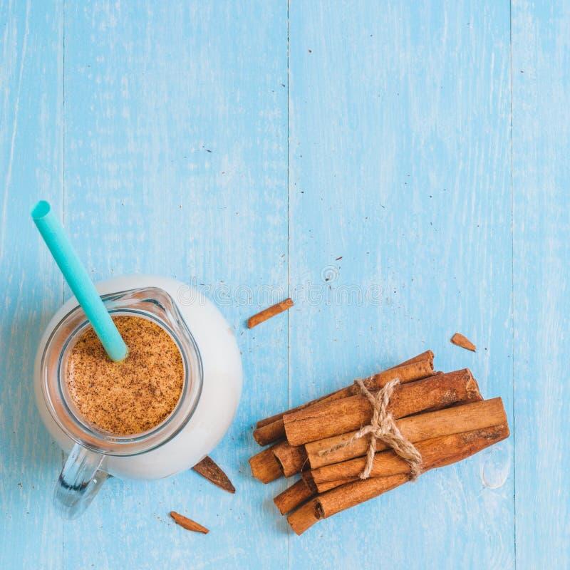Waterkruikglas melk met kaneel en cocktailbuis op blauwe houten achtergrond stock foto