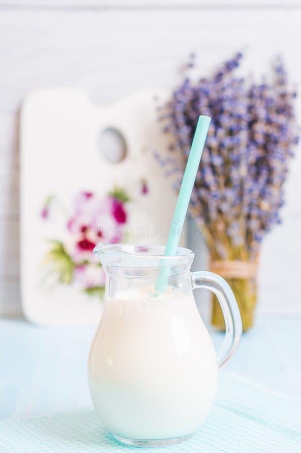 Waterkruikglas melk met lavendel en cocktailbuis op een blauwe houten achtergrond stock fotografie