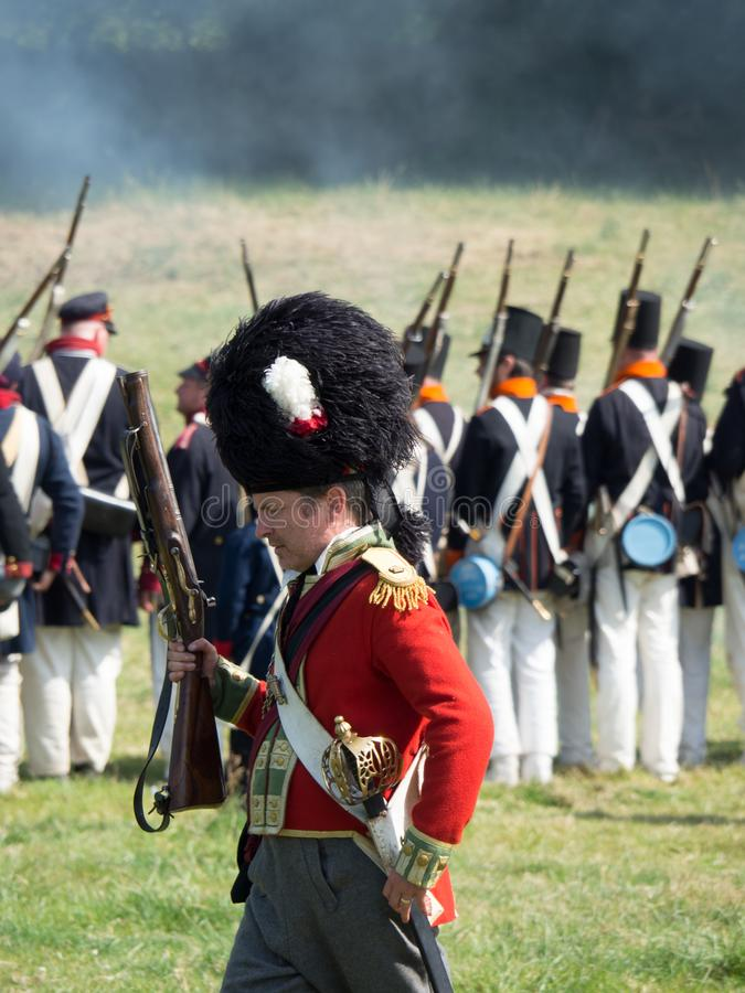 Waterloo, Belgium - June 18 2017: Scenes from the reenactment of. Waterloo, Belgium - June 18 2017: A British soldier with a short musket wears a bearskin during stock image