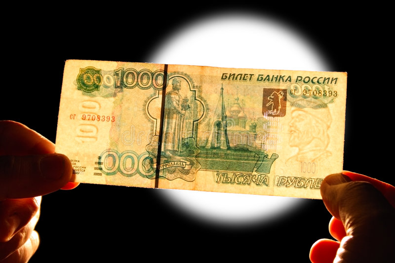 Watermark 1000 rubles. Checking watermark 1000 russian rubles over white lamp isolated on black royalty free stock image