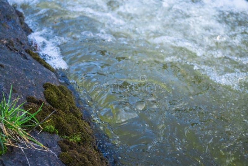 Watermassa Water die over de rots stromen De rivier van de berg stock foto's