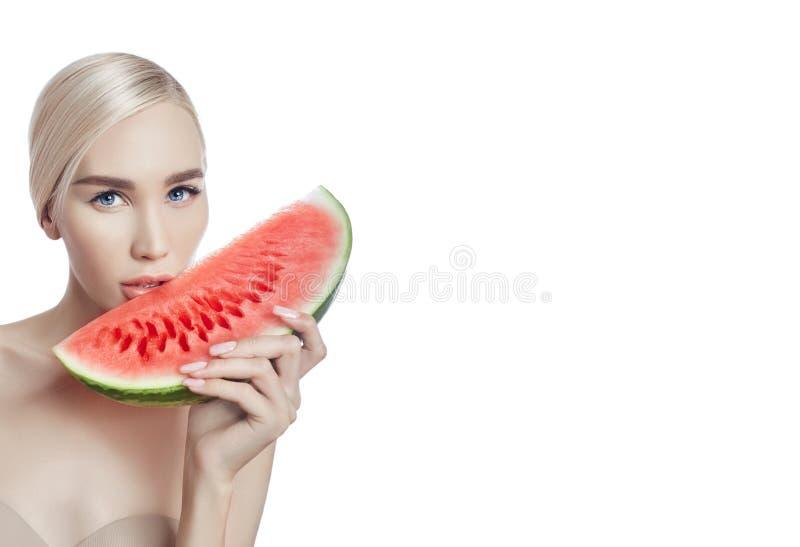 Watermeloen in handen van vrouwen, schone vlotte huid van lichaam en gezicht Blondemeisje in de zomer die een watermeloen in hand royalty-vrije stock afbeeldingen