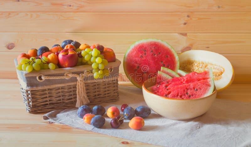 Watermeloen, meloen en rieten mand met verse vruchten op houten lijst Selectieve nadruk royalty-vrije stock afbeelding