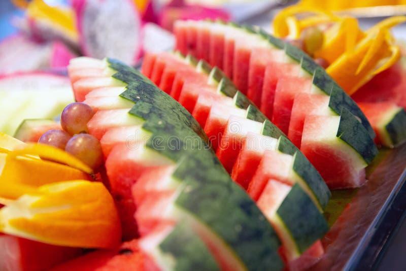 Watermeloen op plaat rode kleur en veel andere vruchten stock foto