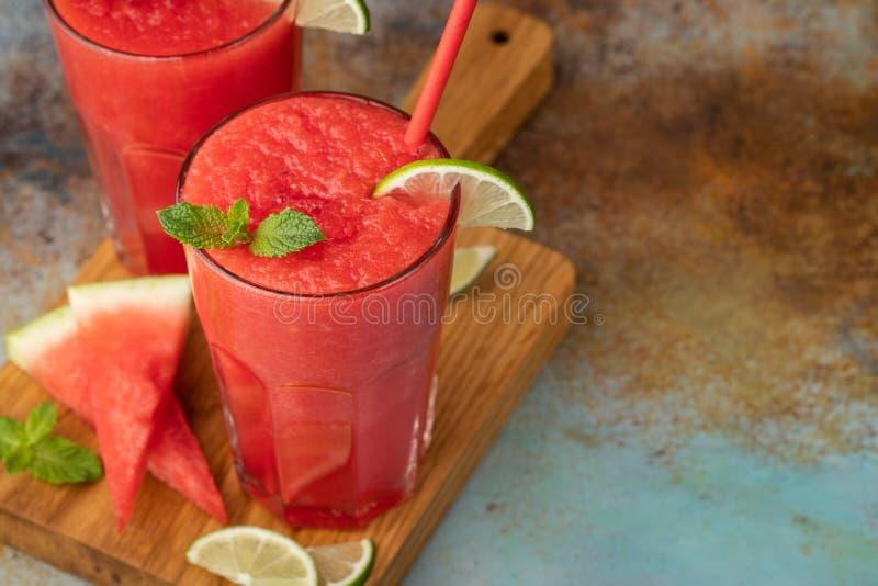 Watermeloen slushie met kalk, de zomer verfrissende drank in lange glazen op een blauwe roestige achtergrond Met exemplaarruimte stock fotografie