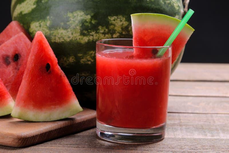 Watermeloen smoothies met watermeloenplakken op een bruine houten lijst en een watermeloen op de achtergrond royalty-vrije stock fotografie