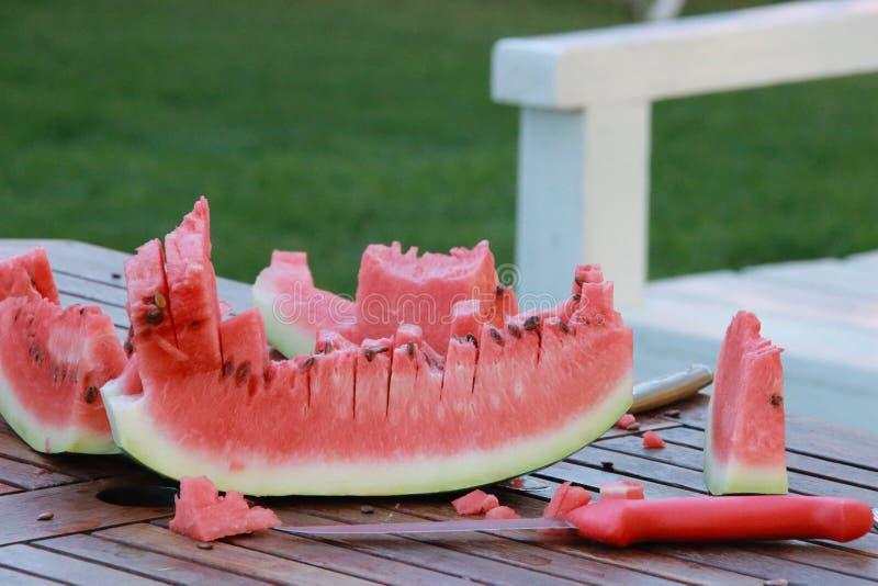 Watermeloenplak op houten lijst met mes stock foto