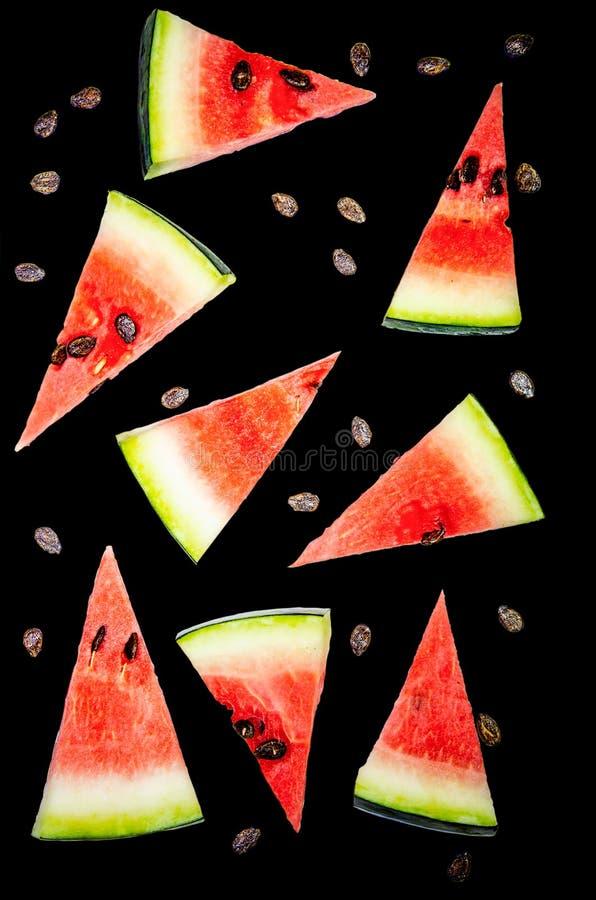 Watermeloenplakken in driehoeken, watermeloenbeenderen worden gesneden dat Zwarte achtergrond royalty-vrije stock foto's