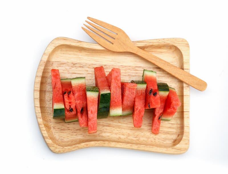 Watermeloenplakken in houten plaat stock afbeeldingen