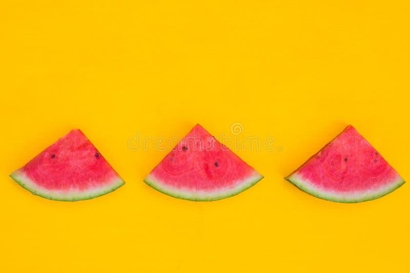 Watermeloenplakken op gele achtergrond met exemplaarruimte, het concept van het de zomerfruit royalty-vrije stock fotografie