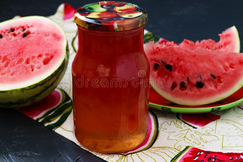 Watermelon canned in sweet syrup in a jar on a dark background royalty free stock image