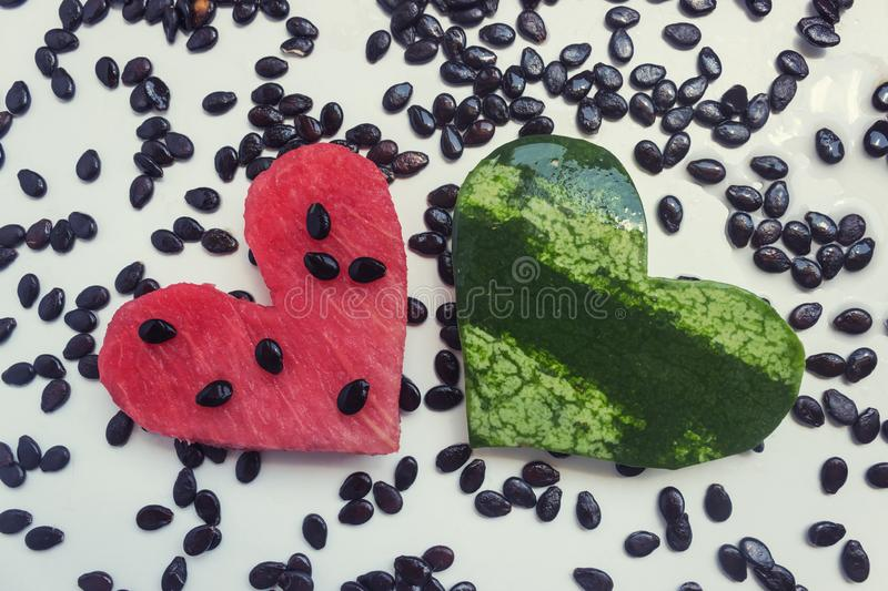 Watermelon, carved in the shape of a heart. On the light table is a lot of watermelon seeds. Concept- summer, love, vegetarianism, raw food stock photos