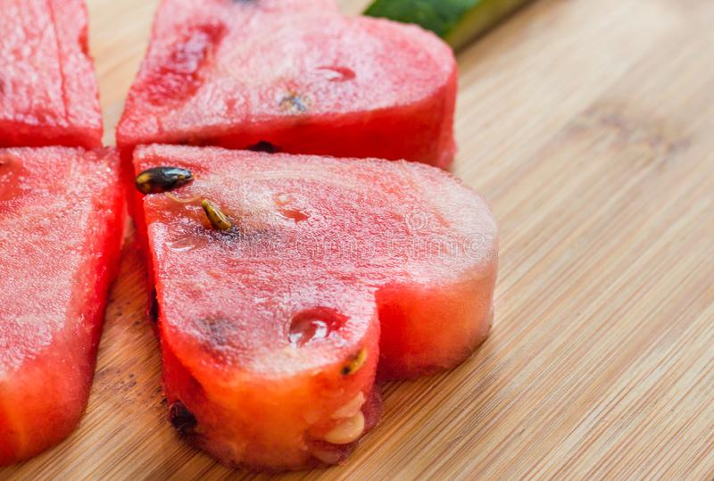 Watermelon citrullus lanatus cut in heart shapes. On a wooden table as close up royalty free stock images