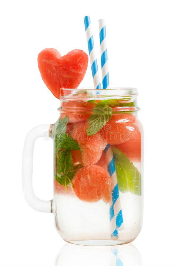 Watermelon cocktail in Mason jar with mint and heart-shaped watermelon slice isolated on white. Background stock photo