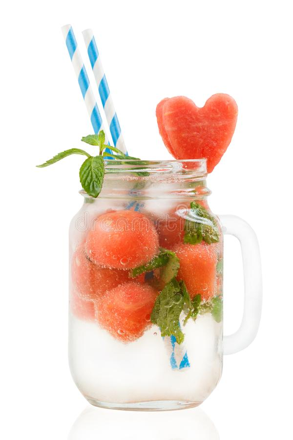 Watermelon cocktail in Mason jar with mint, straws and heart-shaped watermelon slice isolated on white background. Watermelon cocktail in Mason jar with mint stock photo