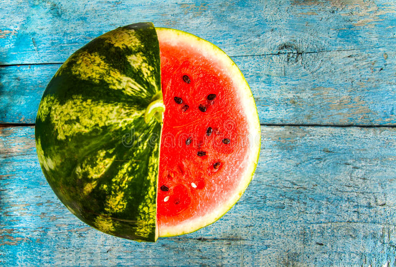 Watermelon with cut a piece of wood lying on a blue rustic backg. Round stock photography