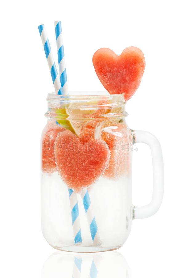 Watermelon drink in Mason jar with straws, heart-shaped watermelon slice isolated on white background. Watermelon drink in Mason jar with straws and heart-shaped royalty free stock photography