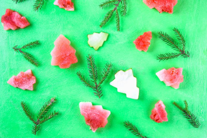 Watermelon in the form of Christmas trees with spruce branches on a green background. Flat lay. Top view. royalty free stock photo