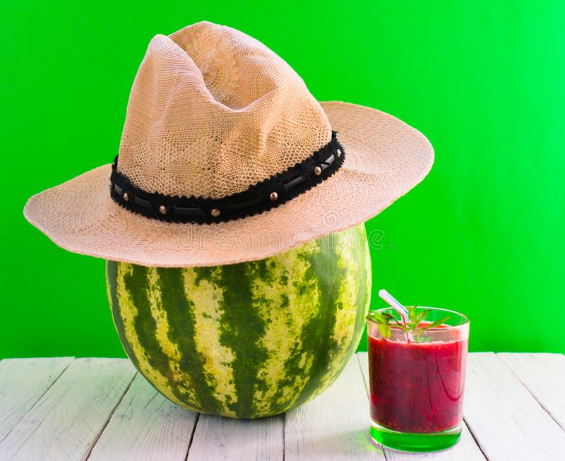 Watermelon in a hat and a glass of juice on a green background. Summer vacation concept. Creative idea of foods and drinks commonl royalty free stock photos
