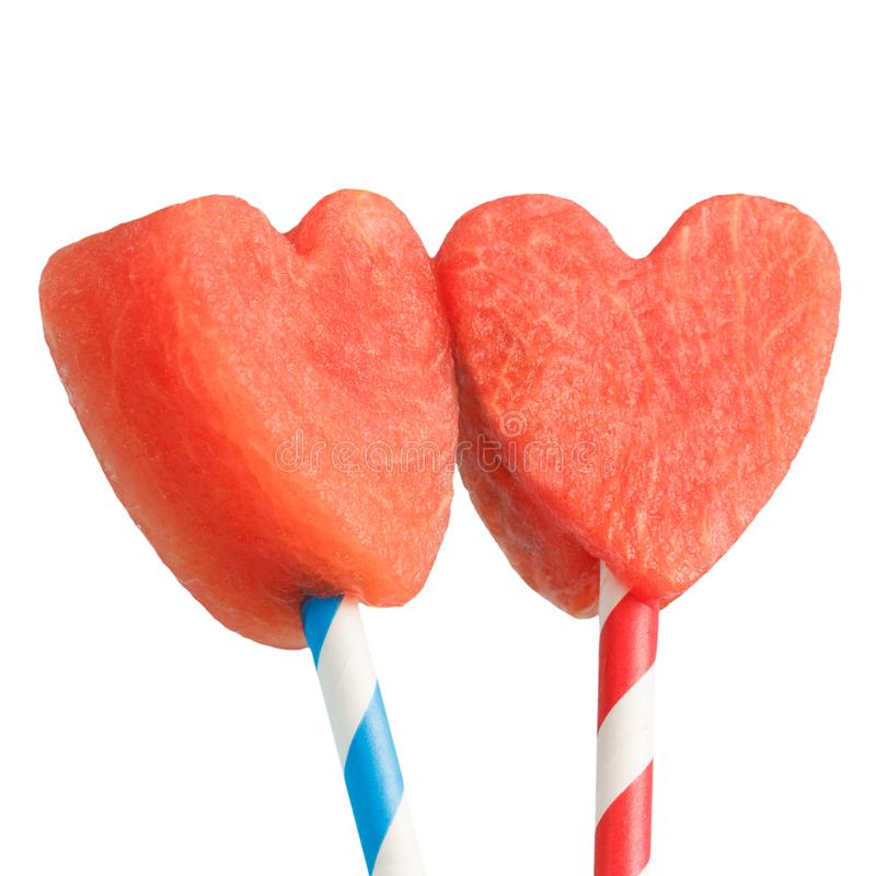 Watermelon heart shaped slices on straws isolated on white background. Valentine`s day sweet dessert concept royalty free stock photography