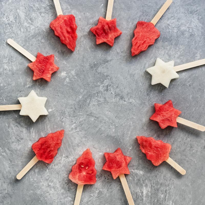Watermelon and melon slice popsicles on gray background. Round frame of popsicles in the shape of a Christmas tree and a star. royalty free stock photos