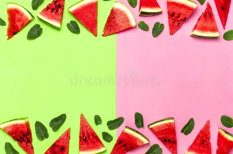 Watermelon pattern. Juicy slices of ripe red watermelon and mint leaves on multicolored pink and green background. Flat lay, top stock images