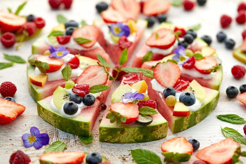 Watermelon pizza with various fresh fruits with the addition of cream cheese, mint and edible flowers. A delicious fruity dessert stock photography