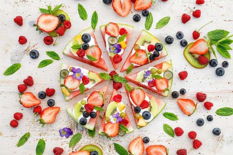 Watermelon pizza with various fresh fruits with the addition of cream cheese, mint and edible flowers. A delicious fruity dessert royalty free stock photography