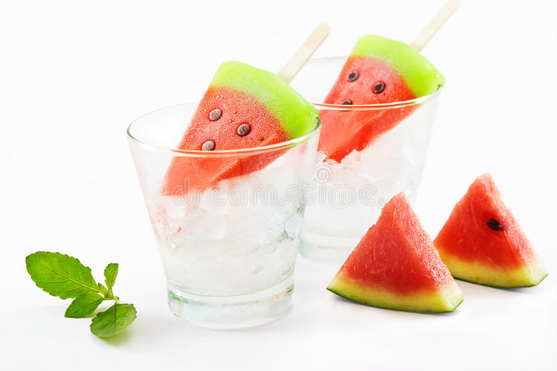 Watermelon popsicles homemade on ice glass and mint white background royalty free stock photo