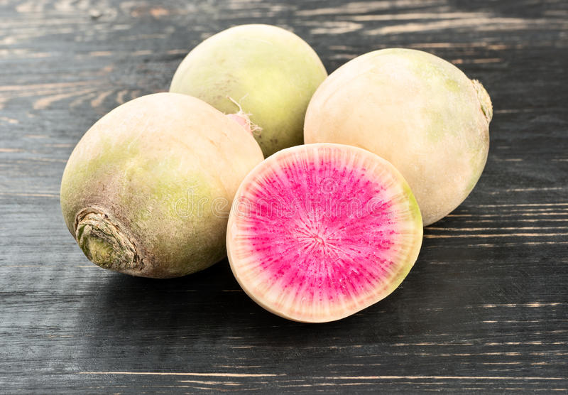 Watermelon radishes and half. Fresh watermelon radishes with half on a wooden background royalty free stock photos
