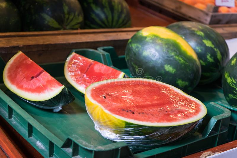 Watermelon ready to sell cut in half and pieces in a green plastic box at local market. Tropical healthy product open to being stock photos