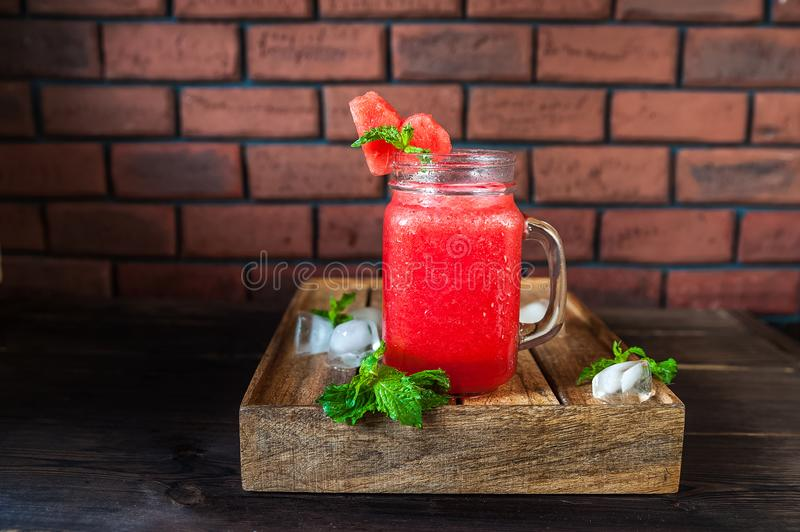 Watermelon refreshing smoothie in a jar close-up and copy space. Watermelon smoothie with a heart of watermelon, mint, ice on a te. Xtured red brick wall stock photos