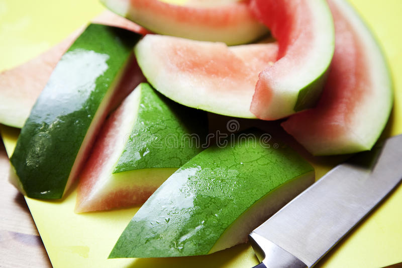 Watermelon Rind on a cutting mat. Chopped up watermelon rind on a cutting mat next to a knife stock photography
