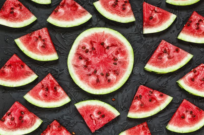 Watermelon, tropical; vegetarian; slices, healthy; diet; dessert. Watermelon. Ripe and juicy watermelon slices on a black stone background. Concept: summer time royalty free stock photos