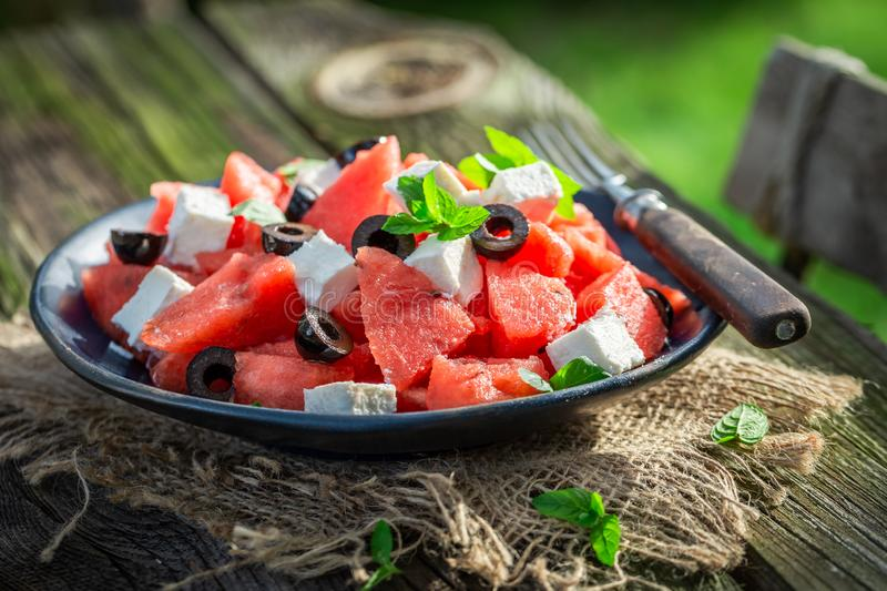 Watermelon salad with black olives and feta cheese in garden. In summer royalty free stock photography