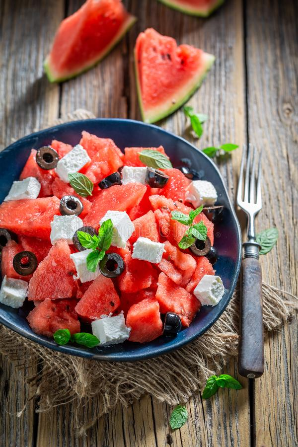 Watermelon salad with feta cheese and black olives. On wooden table stock image